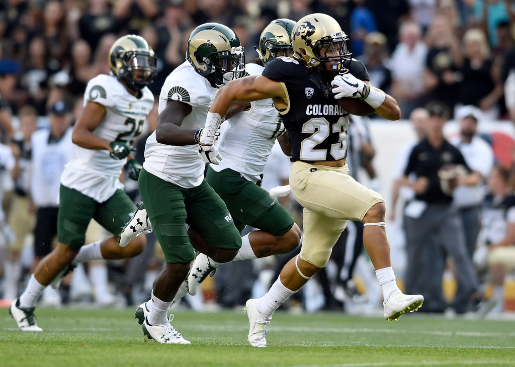 . University of Colorado\'s Phillip Lindsay races past defenders for a touchdown in the first quarter of the Rocky Mountain Showdown against Colorado State University on Friday at Sports Authority Field in Denver. More photos: Buffzone.com Jeremy Papasso/ Staff Photographer/ Sept. 1, 2017