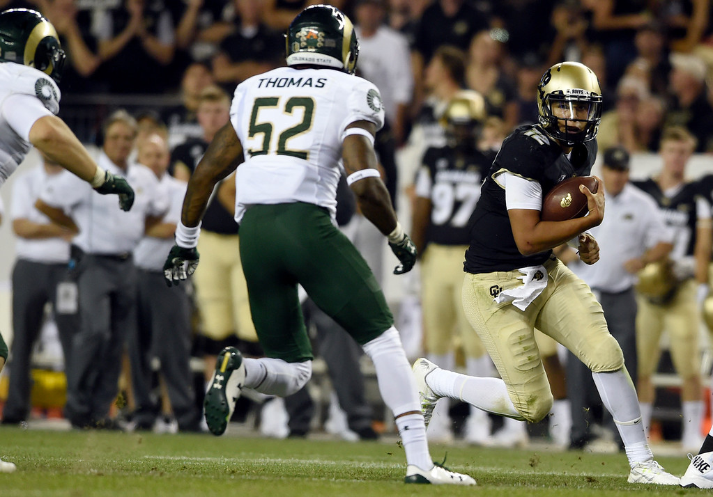 . University of Colorado quarterback Steven Montez rushes the ball during the Rocky Mountain Showdown against Colorado State University on Friday at Sports Authority Field in Denver. More photos: Buffzone.com Jeremy Papasso/ Staff Photographer/ Sept. 1, 2017
