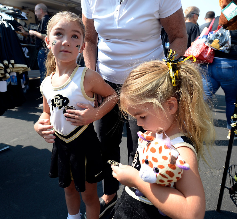 . Charlie Pellant, left, and her sister, Brooklyn, get CU Buff stickers outside the stadium before the CU CSU football game.  Cliff Grassmick / Staff Photographer/ September 1, 2017