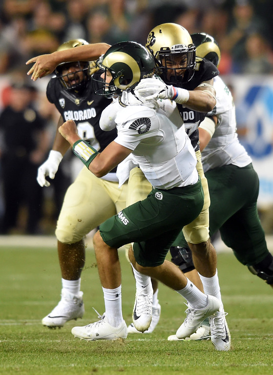 . CSU QB, Nick Stevens, is hit by Drew Lewis, of CU, in the second half of the Rocky Mountain Showdown in Denver.  Cliff Grassmick / Staff Photographer/ September 1, 2017