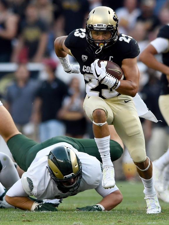 . University of Colorado\'s Phillip Lindsay rushes the ball past a defender during the Rocky Mountain Showdown against Colorado State University on Friday at Sports Authority Field in Denver. More photos: Buffzone.com Jeremy Papasso/ Staff Photographer/ Sept. 1, 2017
