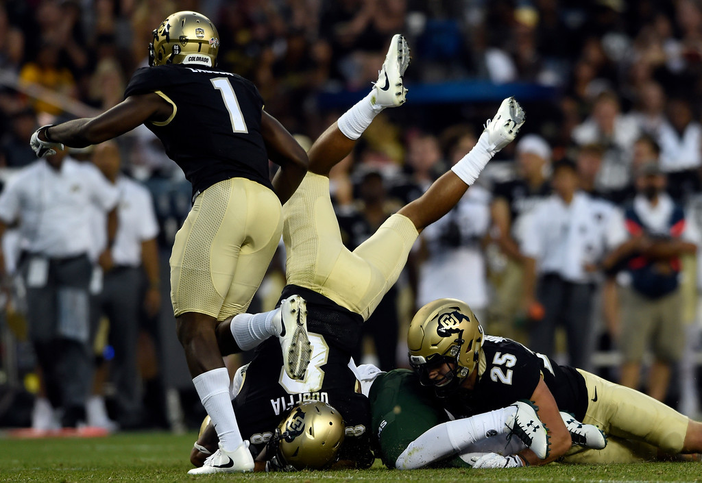 . University of Colorado\'s Trey Udoffia, left, and Ryan Moeller work together to make a tackle during the Rocky Mountain Showdown against Colorado State University on Friday at Sports Authority Field in Denver. More photos: Buffzone.com Jeremy Papasso/ Staff Photographer/ Sept. 1, 2017