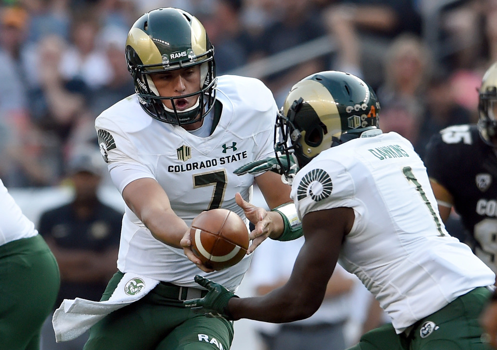 . Colorado State University quarterback Nick Stevens hands off to Dalyn Dawkins during the Rocky Mountain Showdown against theUniversity of Colorado on Friday at Sports Authority Field in Denver. CU won the game 17-3. More photos: Buffzone.com Jeremy Papasso/ Staff Photographer/ Sept. 1, 2017