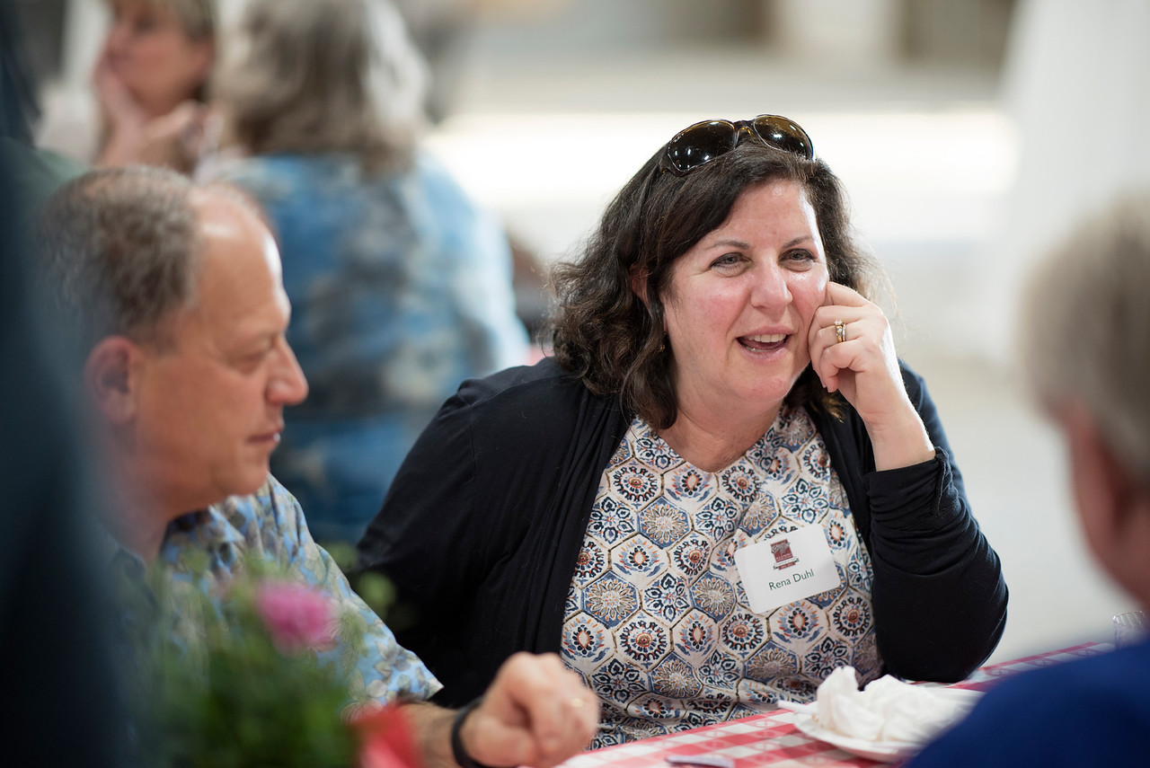 Rena Duhl (center) enjoys a conversation at the Alumni Spring Barbecue that is held at the University Farm on Thursday, April 27, 2017, in Chico, Calif.  (Jessica Bartlett/ Photographer)