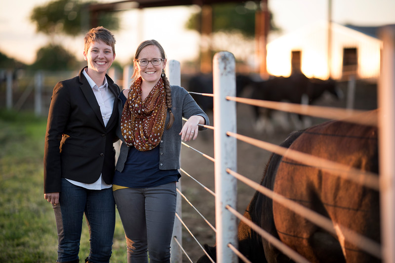 Katherine Post (left) and Ashley Gebb (right) take a photo next to the dairy cows during the Alumni Spring Barbecue that is held at the University Farm on Thursday, April 276, 2017, in Chico, Calif.  (Jessica Bartlett/ Photographer)