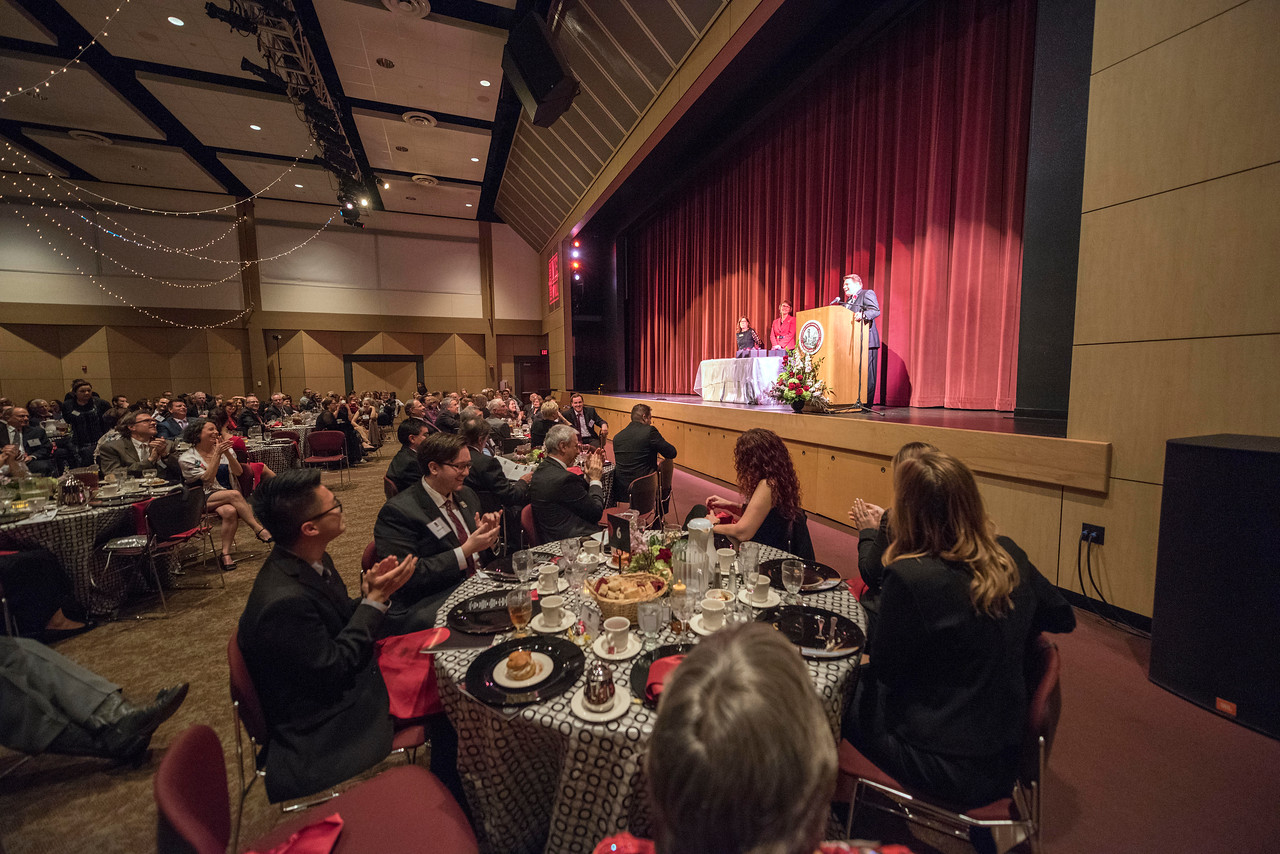 Sue Anderson (left) and President Gayle Hutchinson (center) listen to Distinguished Alumni Michael Finney talk to guests and honorees during the Distinguished Alumni Dinner on Friday, March 24, 2017 in Chico, Calif. (Jason Halley/University Photographer)
