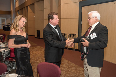 Distinguished Alumni Michael Finney (center)  shakes hand with George Rogers (right) with guests and honorees enjoy the Distinguished Alumni Dinner on Friday, March 24, 2017 in Chico, Calif. (Jason Halley/University Photographer)
