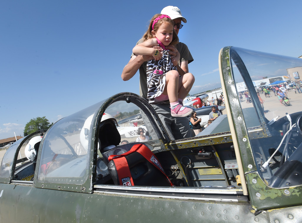 . John Gillis helps Avery Strumberger get into the 1943 Chinese Nanchang CJ6A aircraft.  The Erie Air Fair was held at Erie Municipal Airport on Saturday.  For more photos, go to dailycamera.com.  Cliff Grassmick  Staff Photographer August 12, 2017