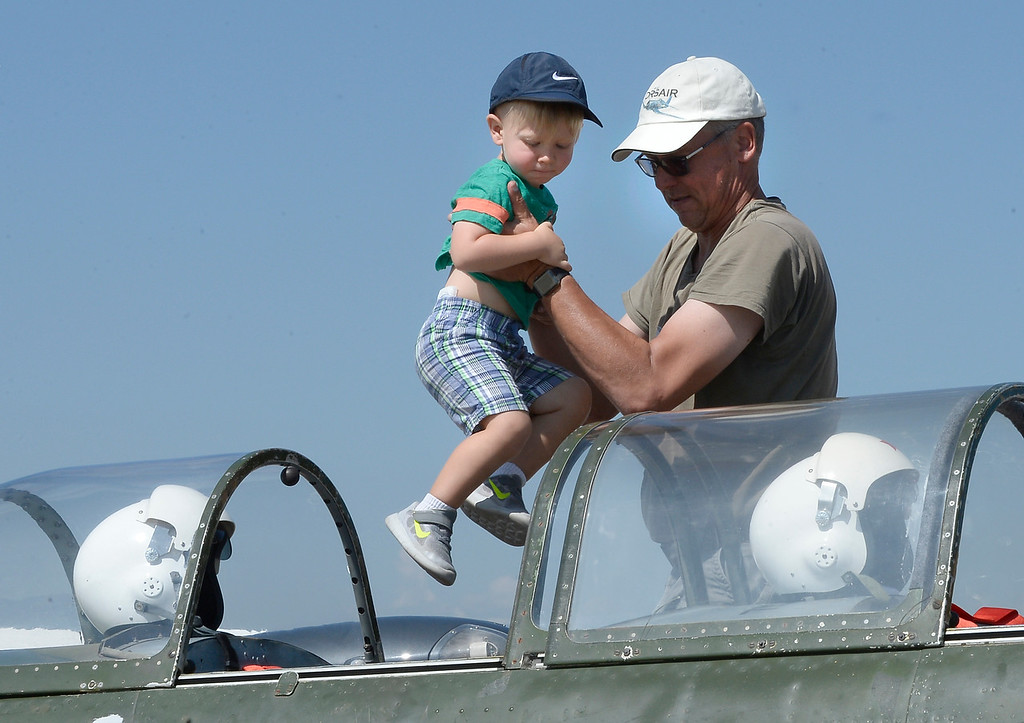 . John Gillis helps Grayson Greenwood get into the 1943 Chinese Nanchang CJ6A aircraft. The Erie Air Fair was held at Erie Municipal Airport on Saturday.  For more photos, go to dailycamera.com.  Cliff Grassmick  Staff Photographer August 12, 2017