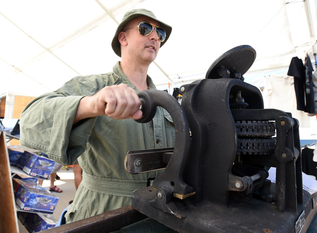 . Greg Kyle makes dog tags for aviation fans at the air fair in Erie. The Erie Air Fair was held at Erie Municipal Airport on Saturday.  For more photos, go to dailycamera.com.  Cliff Grassmick  Staff Photographer August 12, 2017