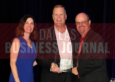 Brad Reid, center accepts Scott & Reid General Contractors's award for being the tie for No. 46 Middle Market 50 company from Melanie Shaffer, left, and Brett lawson of The CFO Suite.