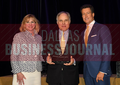 Bill Shaddock, center accepts Capital Title of Texas' award for being the No. 28 Middle Market 50 company from Gemma Descoteaux, left, and Steve Fox of Polsinelli.