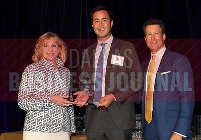 Eric Hage, center accepts Structure Tone Southwest's award for being the No. 30 Middle Market 50 company from Gemma Descoteaux, left, and Steve Fox of Polsinelli.