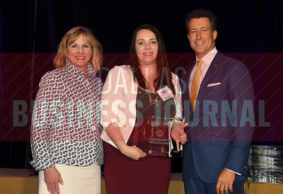 Kelsey Moena, center accepts LiquidAgents Helathcare's award for being the No. 24 Middle Market 50 company from Gemma Descoteaux, left, and Steve Fox of Polsinelli.