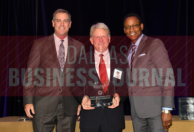 Chris phillips center accepts First National Title Insurance Comapny's award for being the No. 17 Middle Market 50 company from Vance McCollough, left, and Chris Mitchell, Crowe Horwath  Partners.