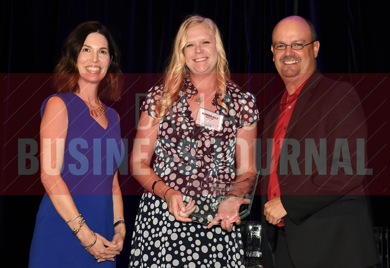 Kimberly Balega, center accepts Conti's award for being the No. 49 Middle Market 50 company from Melanie Shaffer, left, and Brett lawson of The CFO Suite.