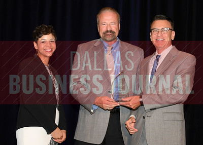 Mike Douglas, CEO of Advent Air-Conditioning Inc. accepts the Torch Award for Ethics in the medium catagory from presenting sponsors Phylissia Clark, left, and Jay Newman of BBB Serving North Central Texas.