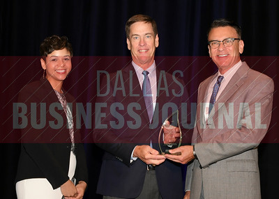 Patrick Kunz, president of Halff Associates accepts the Torch Award for Ethics in the large catagory from presenting sponsors Phylissia Clark, left, and Jay Newman of BBB Serving North Central Texas.