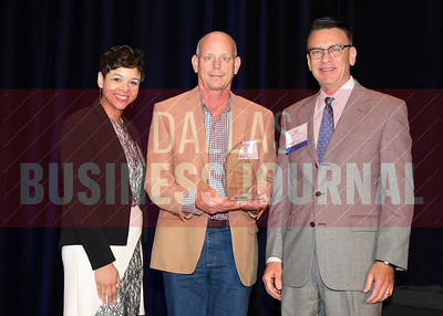 Kevin Key, owner of Key Residential accepts the Torch Award for Ethics in the extra-small catagory from presenting sponsors Phylissia Clark, left, and Jay Newman of BBB Serving North Central Texas.