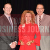 Sara Madsen Miller of 1820 Productions, center, is presented with her Women in Business Award from Brian Enzler, Market Executive, BMO Harris Bank, left, and Bill Hethcock of the Dallas Business Journal.