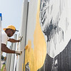 Buffalo State College alumni Edreys Wajed working on The Freedom Wall mural.