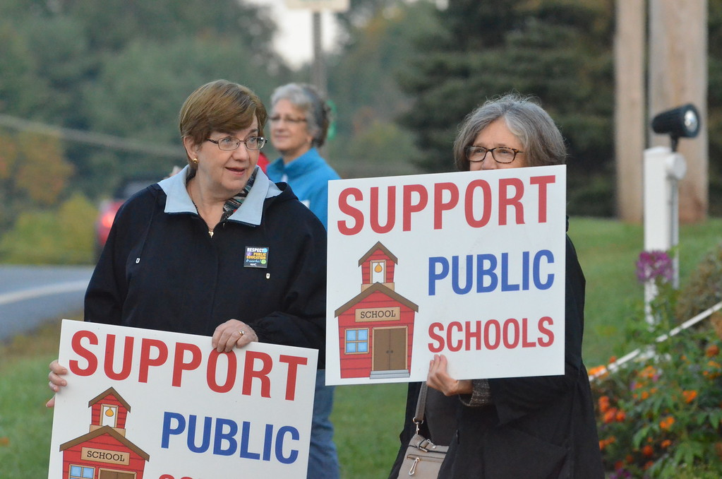 . Leah McDonald - Oneida Daily Dispatch Public school supporters hold signs at the corner of Seneca Street and Route 5 on the first day of school on Thursday, Sept. 7, 2017.
