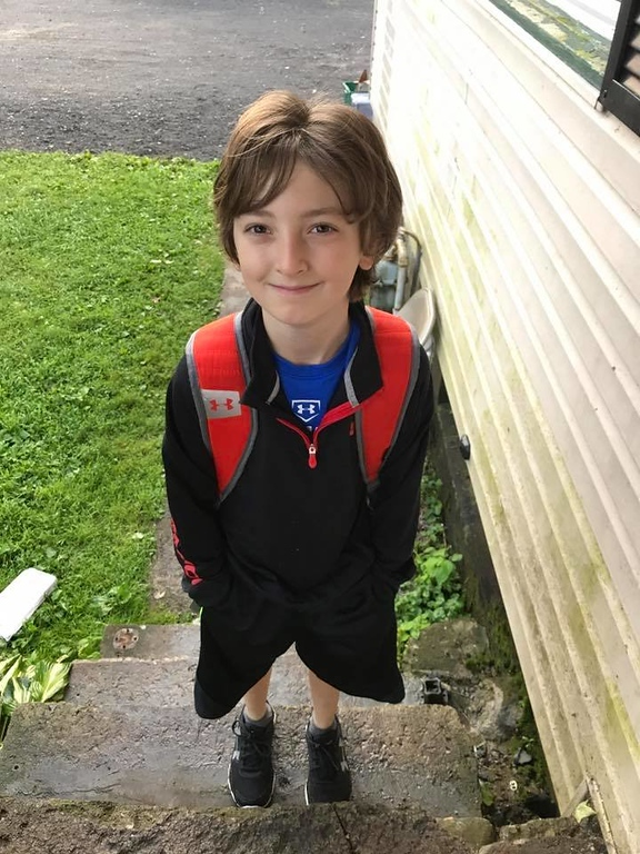 . Photo Courtesy Crystal Curtis James McCray poses outside his Canastota home before heading off to fifth grade.