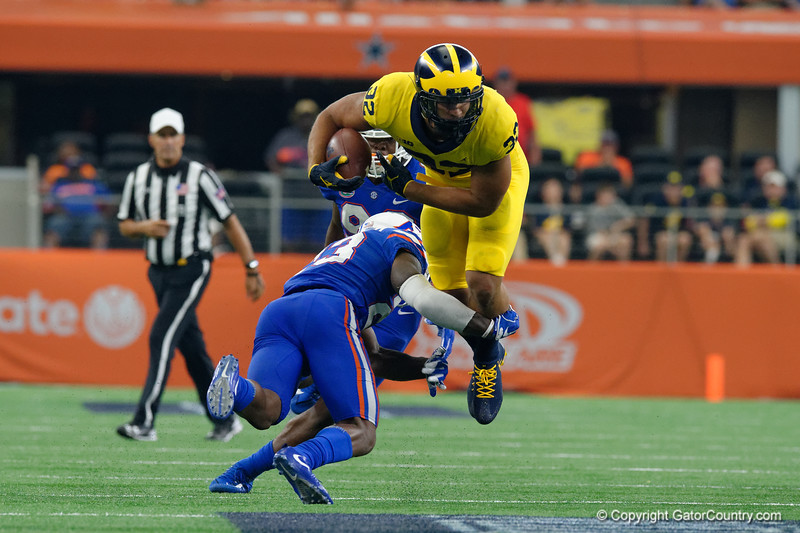 Michigan running back Ty Isaac is hit by University of Florida Gators defensive back Chauncey Gardner, Jr.  during the first half of the 2017 Advocare Classic at AT&T Stadium in Dallas, Texas as the Florida Gators take on the Michigan Wolverines. September 2nd, 2017.  Gator Country photo by David Bowie.