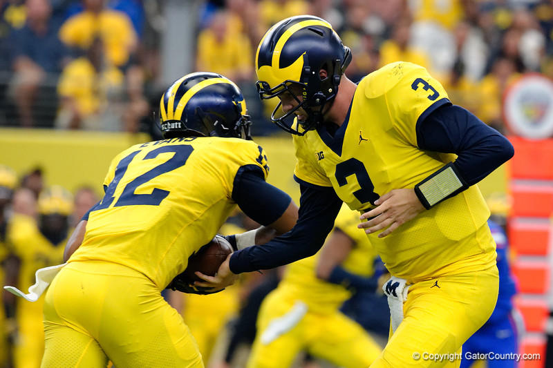 Michigan quarterback Wilton Speight turns and hands the ball off to Michigan running back Michigan running back Chris Evans during the first half of the 2017 Advocare Classic at AT&T Stadium in Dallas, Texas as the Florida Gators take on the Michigan Wolverines. September 2nd, 2017.  Gator Country photo by David Bowie.