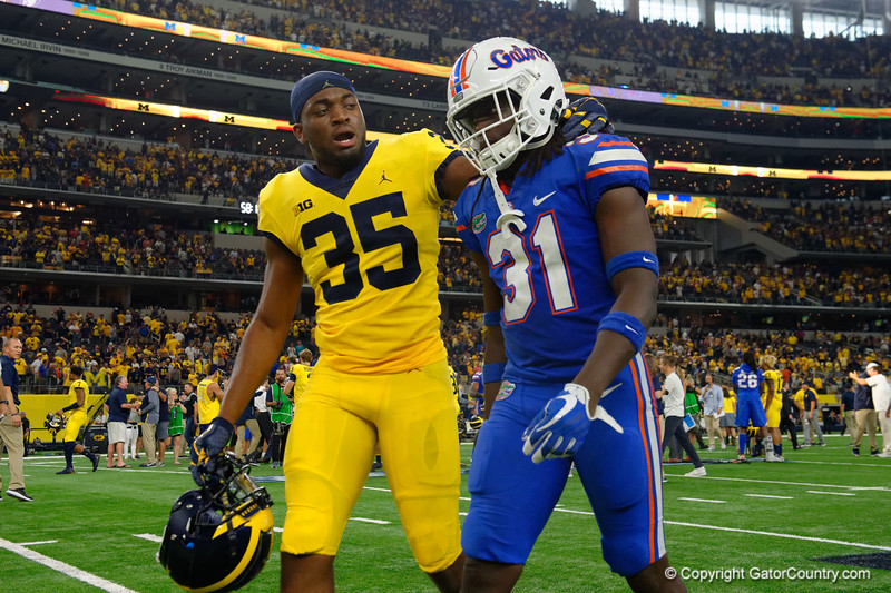 Michigan linebacker Josh Uche consoles University of Florida Gators defensive back Shawn Davis during post-game of the 2017 Advocare Classic at AT&T Stadium in Dallas, Texas as the Florida Gators take on the Michigan Wolverines. September 2nd, 2017.  Gator Country photo by David Bowie.