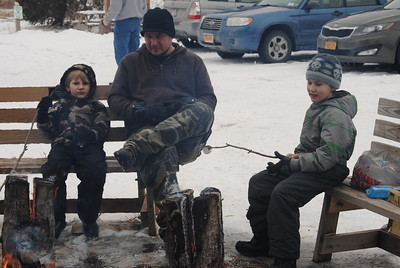 Leah McDonald - Oneida Daily Dispatch Damian Kimball, 4, left, dad Rob Kimball, and brother Gavin Kimball, 9, roast marshmallows at the Winter Hibernation Festival at the Great Swamp Conservancy in Canastota, N.Y., on Saturday, Feb. 11, 2017.