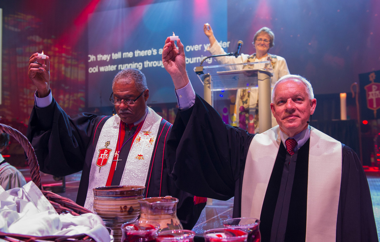 Bishop Julius C. Trimble (left) and Rev. Larry Whitehead hold candles aloft at the Service of Remembrance and Communion at 2017 INUMC Annual Conference in Indianapolis