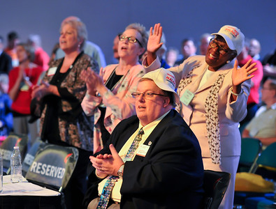 Chris Newman-Jacobs (left), Michelle Cobb, and John Groves clap to music at the Friday Plenary at the 2017 INUMC Annual Conference in Indianapolis.