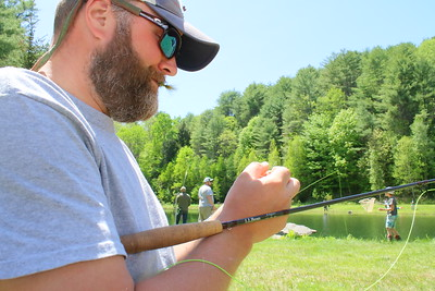 IMG_3204 brian burkholder of Barnard holds a fly in his mouth while changing flys,,is with Trout Unlimited