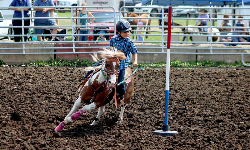 Vincent Stewart, 9, rides his horse Zuma around the poles during the exhibition poles competition at the Kendall County Fair on Thursday, Aug. 3.