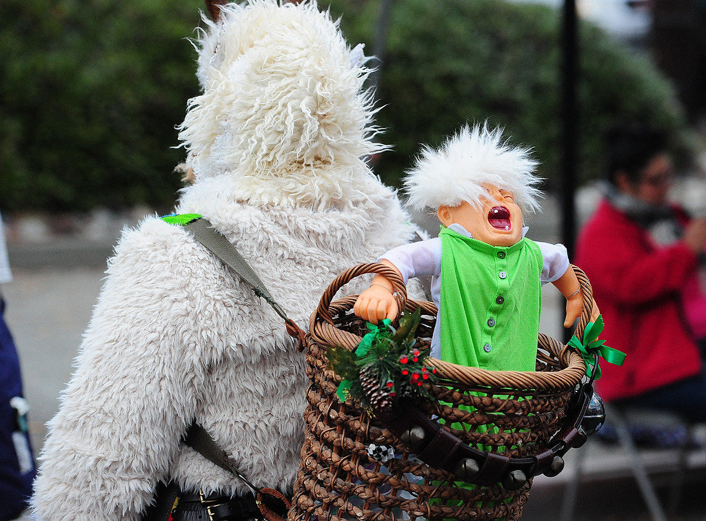 . VALLEJO, CA- DEC. 2, A member of Beast Bay Krampus carries a screaming baby before the start of the Mad Hatter Holiday Parade in downtown Vallejo on Saturday. (CHRIS RILEY/Times-Herald)