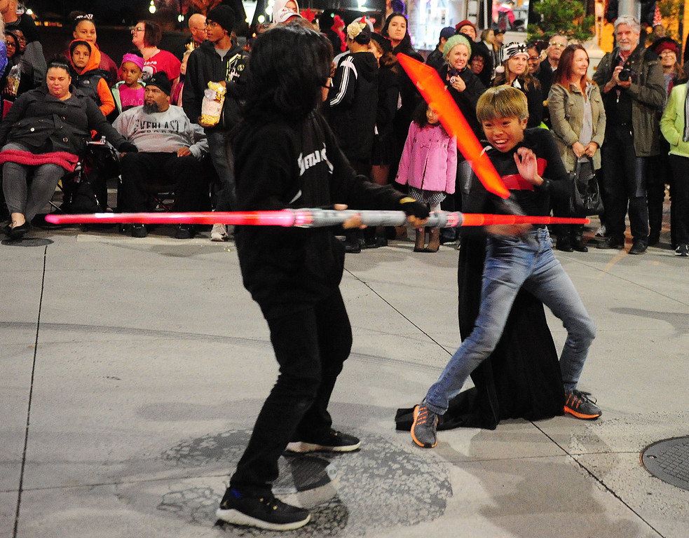 . VALLEJO, CA- DEC. 2, Roman Gamboa and Jared Bergonia fight with lightsabers as the perform with the Island Warriors during the Mad Hatter Holiday Parade in downtown Vallejo on Saturday. (CHRIS RILEY/Times-Herald)