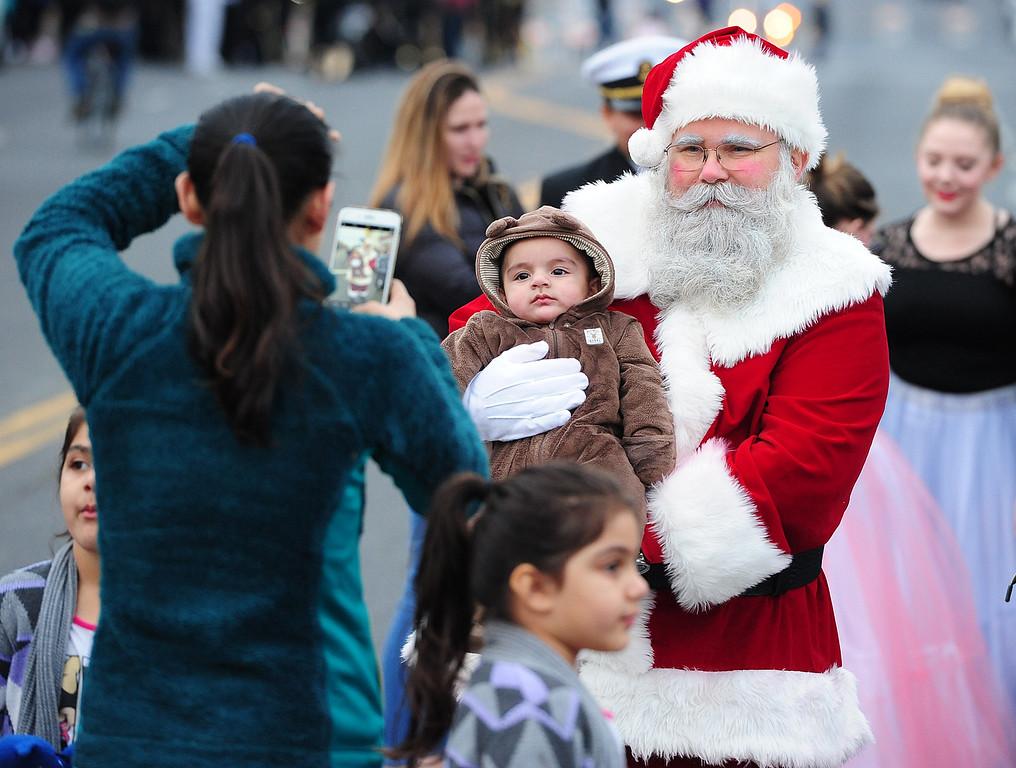 . VALLEJO, CA- DEC. 2, Tom Bilbo, dressed as Santa, takes pictures with a baby during the Mad Hatter Holiday Parade in downtown Vallejo on Saturday. (CHRIS RILEY/Times-Herald)