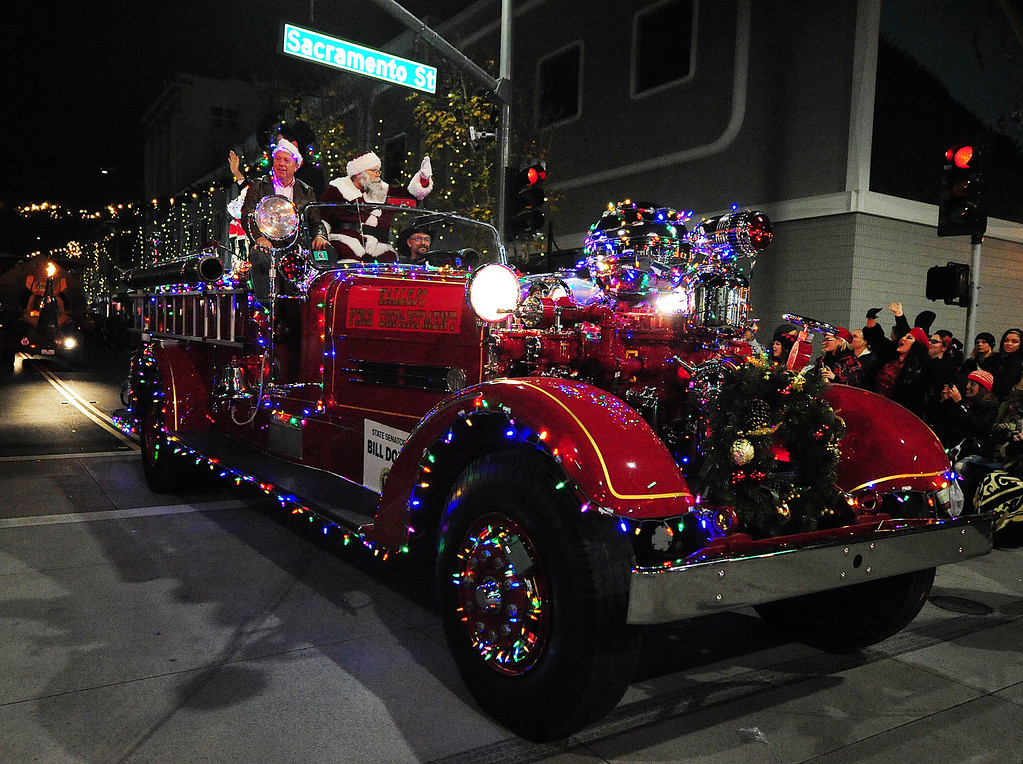 . VALLEJO, CA- DEC. 2, Senator Bill Dodd rides in a vintage fire truck with Santa, played by Tom Bilbo during the Mad Hatter Holiday Parade in downtown Vallejo on Saturday. (CHRIS RILEY/Times-Herald)