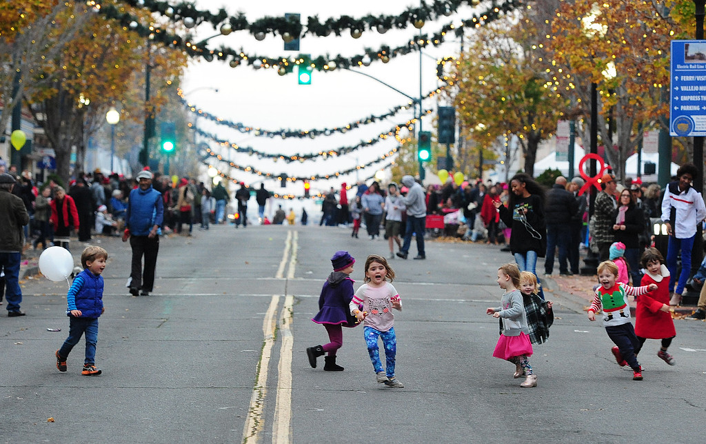 . VALLEJO, CA- DEC. 2, Small children play and dance on Georgia Street before the start of the Mad Hatter Holiday Parade in downtown Vallejo on Saturday. (CHRIS RILEY/Times-Herald)