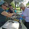 Roger Schneider | The Goshen News<br /> Nadia Kulish, left, of Goshen serves Jan Johnson of Goshen some crepes with cheese at the Goshen Multicultural Festival Saturday at Rogers Park.