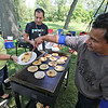 Roger Schneider | The Goshen News<br /> Foods from Spanish-speaking countries were popular at Saturday's Goshen Multicultural Festival. Radio Horizonte Lavoz de Goshen sponsored a food booth and Taide Galvez, left, Felipe Abad, center and Carlos Lopez keep the  pupusas moving from the grill to customers.