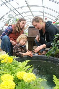 IMG_2224 kat robbins and son Jasper, 2, feed goldfish with teaching assistnat Christine Frohloff, ,in pond made by senior Cole Westcott