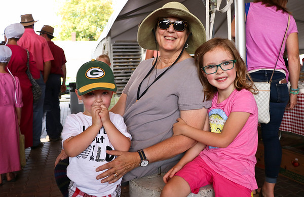 LEANDRA BEABOUT | THE GOSHEN NEWS<br /> A family of first-time visitors to the Nappanee Apple Festival took a break in the shade. From left: Henry Kelly, 3, Warsaw; Patty Wallesverd of Iron Ridge, WI; Emma Kelly, 5, Warsaw.