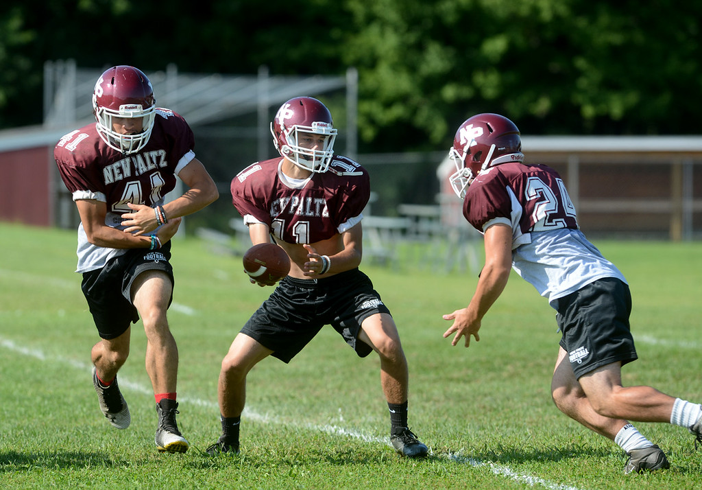 . Tania Barricklo-Daily Freeman                       Quarterback Jimmy Verney fakes a pass to Axel Rodriguez  and hands off to Christian Burda