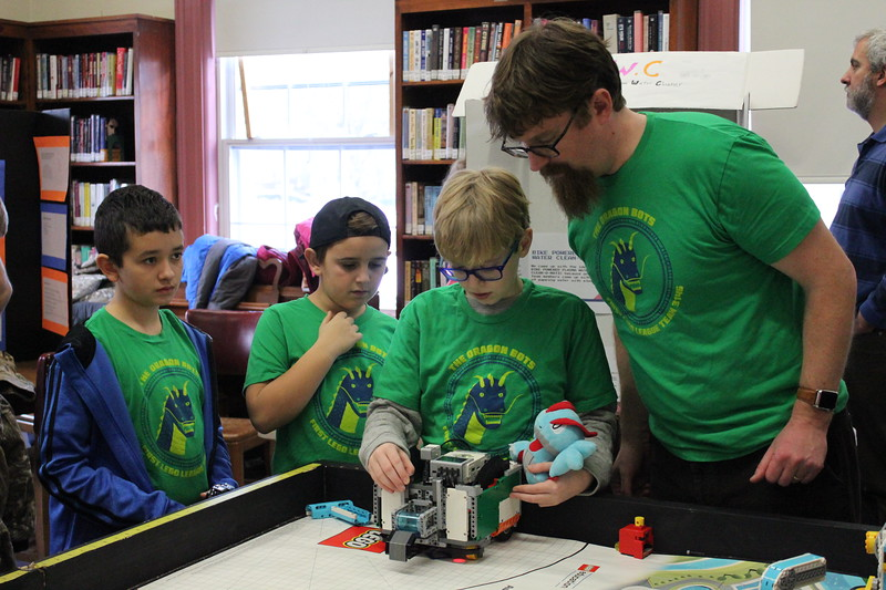 Charles Pritchard - Oneida Daily Dispatch Team Dragon Bots look over their program one more time before sending their robot on Thursday, Dec. 28, 2017.