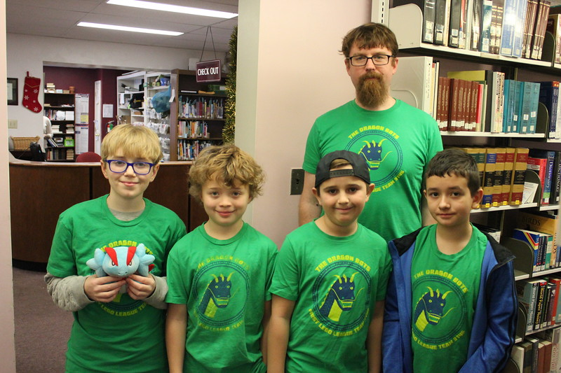 Charles Pritchard - Oneida Daily Dispatch Eli Davis, left, James Dillon, left-middle, David Goodfriend, right-middle, Gideon Dreier and Coach Shelby Davis of the Dragon Bots at the Oneida Public Library on Thursday, Dec. 28, 2017.