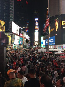 Times Square at night.  That small blue ball above the clock straight ahead is the ball that drops at midnight on New Year's Eve.