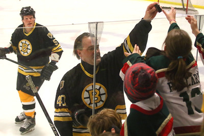 PHOTO BY HERB SWANSON:           Bruce Shoebottom hands a puck to kids before the start of the Boston Bruins Alumni vs the Union Arena Bears game at Union Arena  in Woodstock, Vermont on Saturday, February 25, 2017. http://herbswanson.smugmug.com/