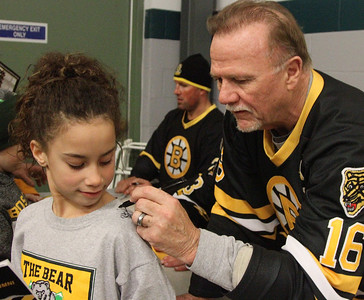 PHOTO BY HERB SWANSON:             Rick Middleton signs his autograph on Lexi Mosher's shirt  at the Boston Bruins Alumni vs  Union Arena Bears game at Union Arena  in Woodstock, Vermont on Saturday, February 25, 2017. http://herbswanson.smugmug.com/